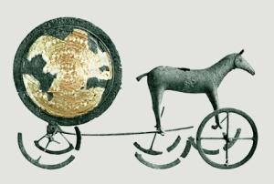 """Sonnenwagen, Rainer Zenz, gemeinfrei. """"Ob die Mythen inhaltlich irgendetwas mit dem zu tun haben, was auf uns überkommen ist, lässt sich nicht feststellen. Das Rad mit vier Speichen als Felsritzung lässt manche auf einen Sonnenkult in der Bronzezeit schließen, für den eine mythische Grundlage aber nicht überliefert ist. Das Gleiche gilt für Miniaturäxte, die mit dem Blitz in Verbindung gebracht werden. Der Sonnenwagen von Trundholm, ein 1902 auf Sjælland in Dänemark gefundenes 57 cm langes Bronzemodell eines von Pferden gezogenen Wagens, der in die Zeit von 1500 bis 1300 v. Chr. datiert wird, belegt jedenfalls keinen Sonnenkult."""""""